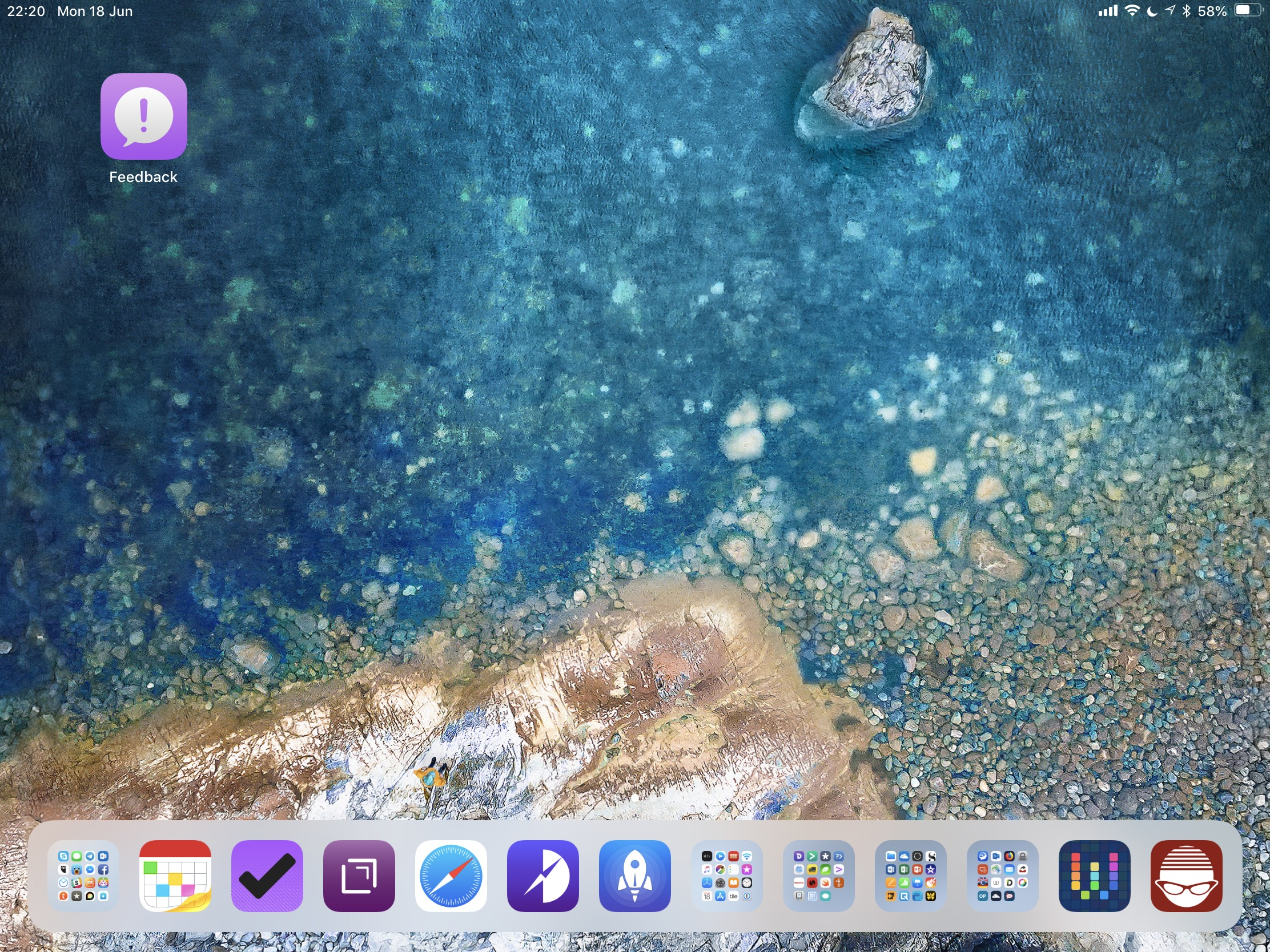 Homescreen with blue beach background, feedback icon top right, and all other apps in the dock